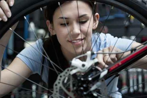 Woman repairing bicycle wheel in repair shop (Source: http://abqthemag.com)
